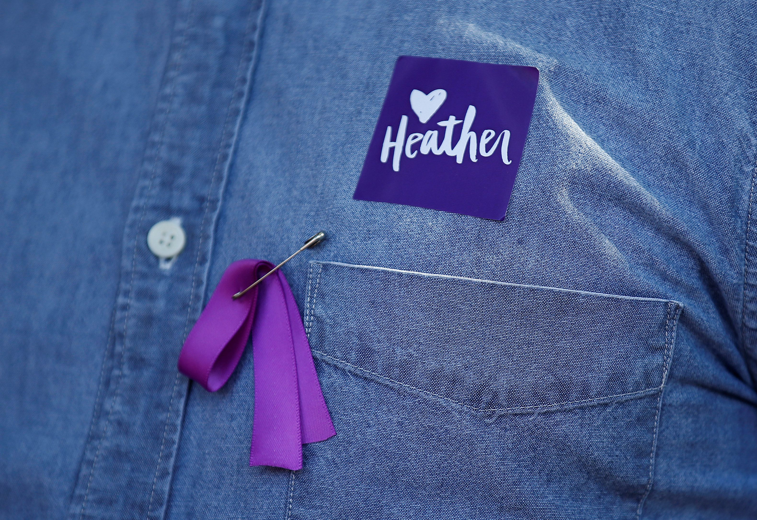 A man wears a purple ribbon to remember Heather Heyer, who was killed protesting during a white supremacist rally, as he