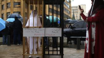 TOPSHOT - An activist from the Lebanese NGO Abaad (Dimensions), a resource centre for gender equality, dressed as a bride and wearing bandages stands in a golden cage during a protest near the parliament in downtown Beirut on March 15, 2017, as MPs are debating a vote against article 522 in the Lebanese penal code.  The article shields rapists from prosecution on the condition that they marry their victim, a phenomenon that is still practised in the country, especially among conservative families whose chief aim is to preserve the family's so-called 'honour. / AFP PHOTO / PATRICK BAZ        (Photo credit should read PATRICK BAZ/AFP/Getty Images)