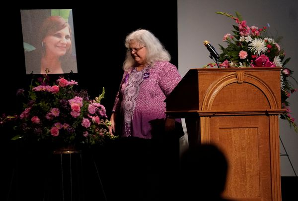 Heather Heyer's mother, Susan Bro, walks by a picture of her daughter after speaking at her memorial service.