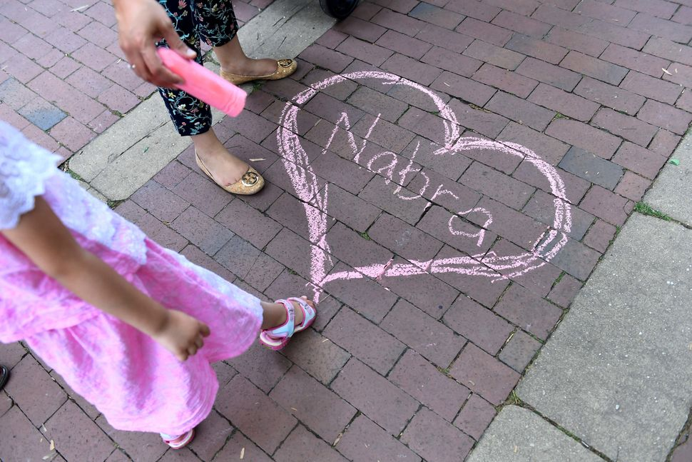 Nabra Hassanen's name appears in chalk at a vigil at on June 21 near Reston, Virginia.
