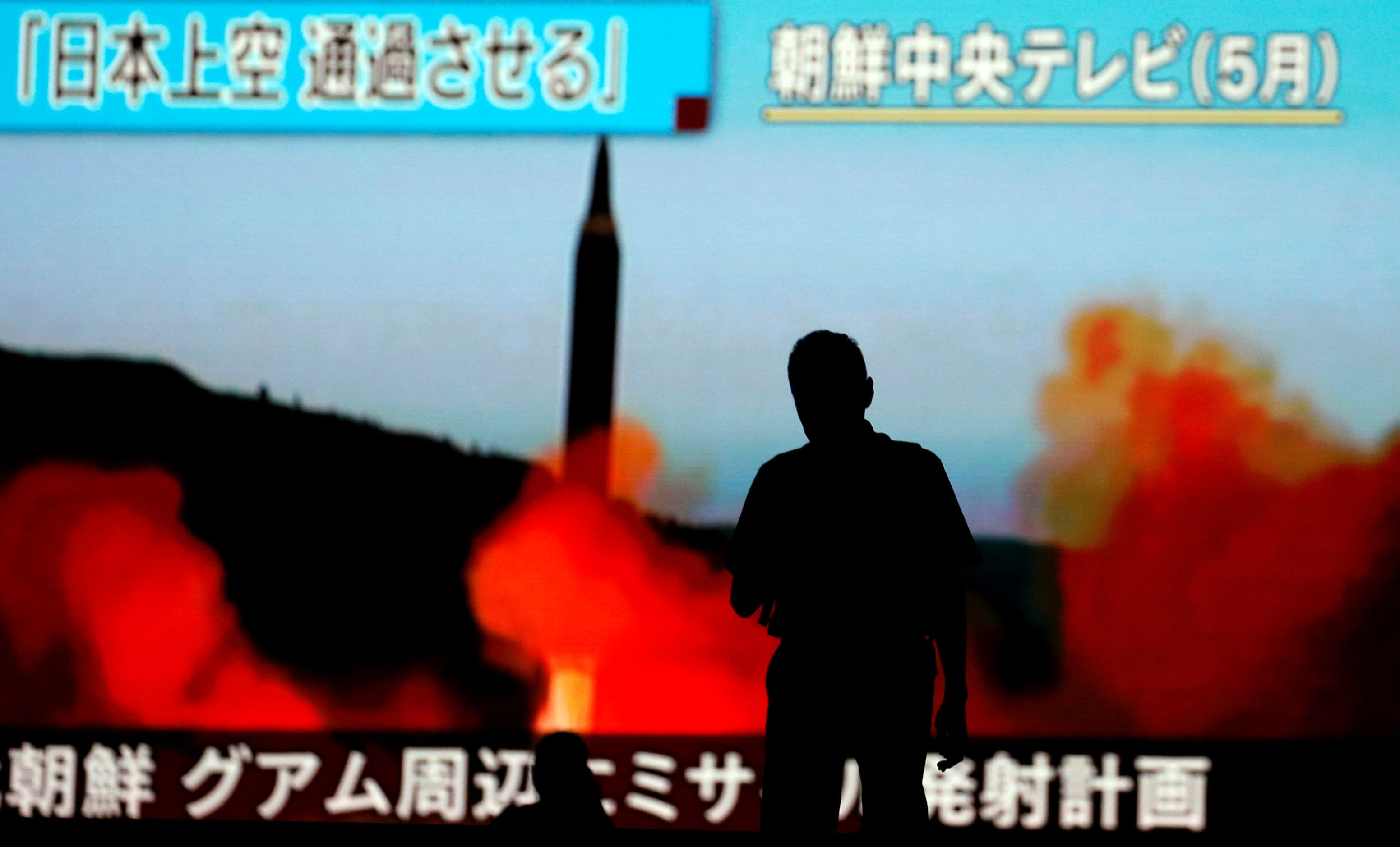 A man walks in front of a monitor showing news of a fresh North Korea threat. Tokyo, Japan. Aug. 10, 2017.