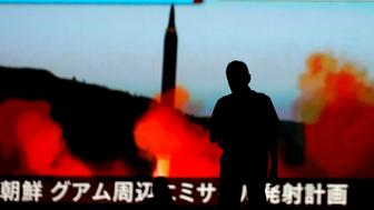 A man walks in front of a monitor showing news of North Korea's fresh threat in Tokyo, Japan, August 10, 2017.  REUTERS/Toru Hanai