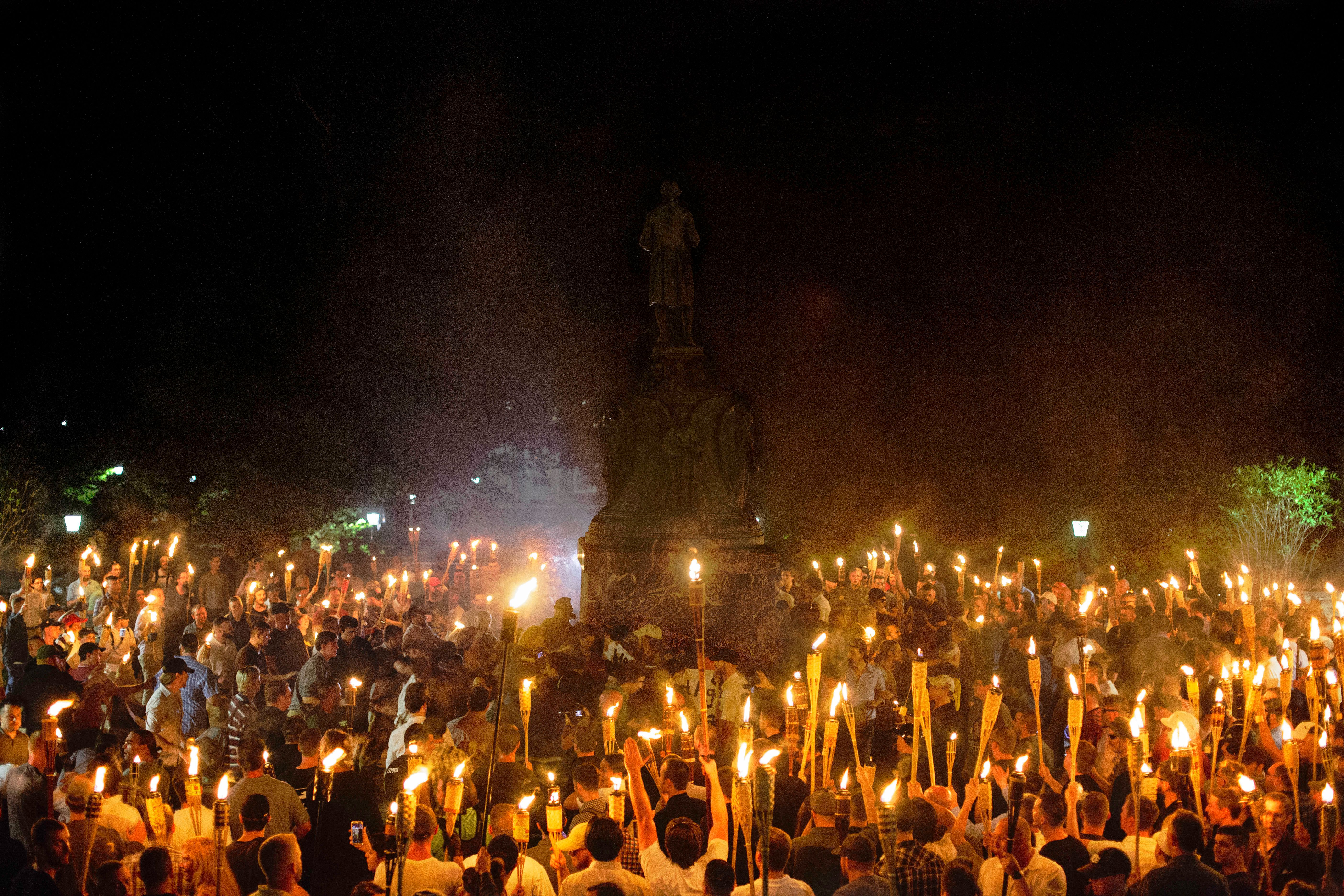 Neo Nazis, Alt-Right, and White Supremacists encircle counter protestors at the base of a statue of Thomas Jefferson after marching through the University of Virginia campus with torches in Charlottesville, Va., USA on August 11, 2017 (Photo by Shay Horse/NurPhoto via Getty Images)