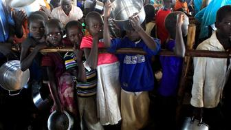 South Sudanese refugee children hold their pots as they wait to be served porridge at the Palabek Refugee Settlement Camp in Lamwo district, Uganda June 16, 2017. Picture taken June 16. REUTERS/James Akena