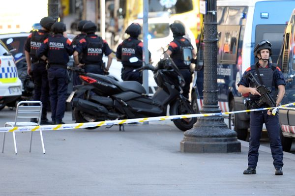 Armed policemen stand in a cordoned-off area.