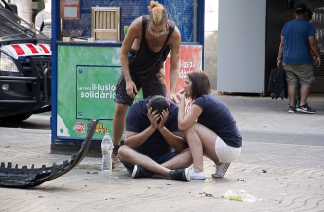 People react after a van crashed into pedestrians in a crowded and popular tourist area in Barcelona