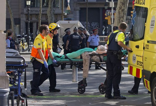 Police officers and emergency service workers move an injured person into an ambulance.