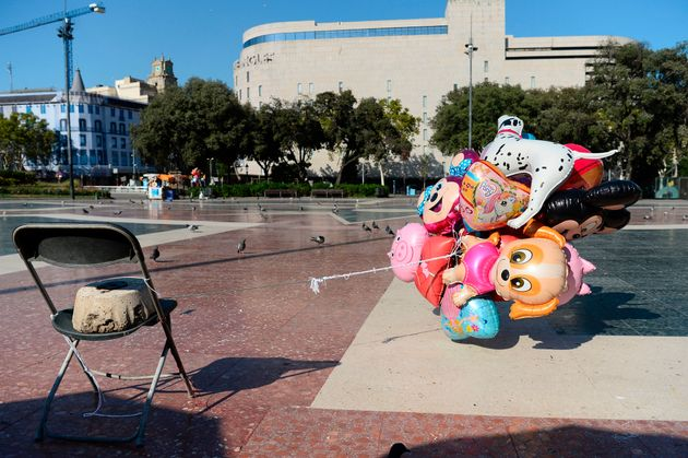 Abandoned air balloons of a street vendor tied to a chair fly at the empty Plaza de Catalunya after the