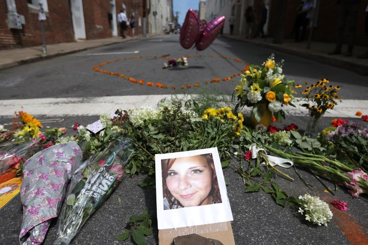 Flowers surround a photo of 32-year-old Heather Heyer, who was killed when a car plowed into a crowd of people protesting aga