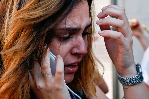 A woman cries as she talks on the phone.
