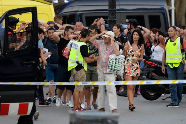 People put their hands up as police check their identities near the scene of the attack.