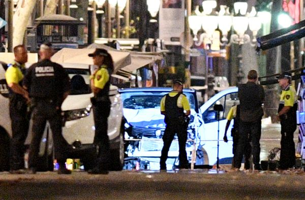 A damaged van, believed to be the one used in the attack, is surrounded by police officers.