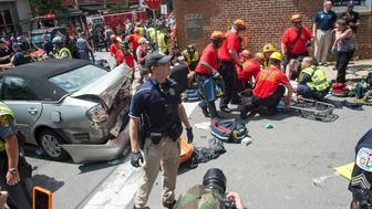 A woman is received first-aid after a car accident ran into a crowd of protesters in Charlottesville, VA on August 12, 2017.  A picturesque Virginia city braced Saturday for a flood of white nationalist demonstrators as well as counter-protesters, declaring a local emergency as law enforcement attempted to quell early violent clashes.  / AFP PHOTO / PAUL J. RICHARDS
