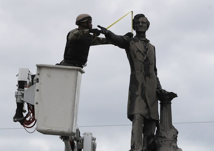 A New Orleans city worker wearing body armor and a face covering measures the Jefferson Davis monument on May 4 after a Louis