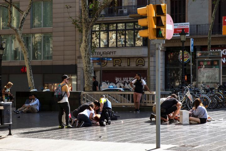 Injured people are tended to near the scene of a terrorist attack in the Las Ramblas area Thursday in Barcelona.