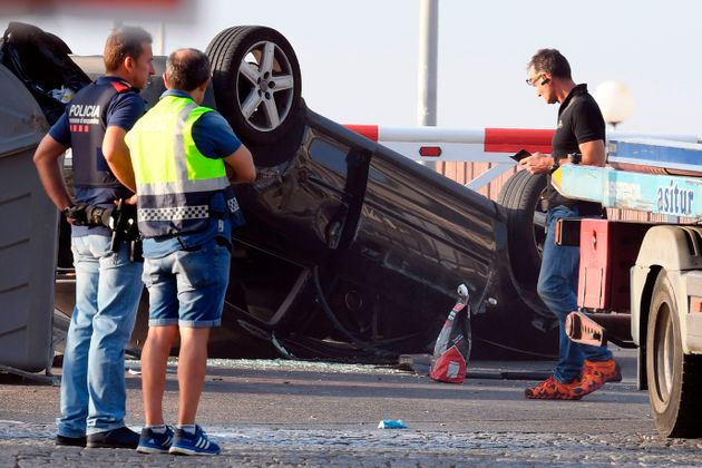 Policemen check a car involved in a terrorist attack in Cambrils, a city 120 kilometres south of