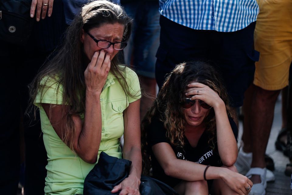 People gather to mourn at Las Ramblas, a tree-lined street popular with tourists, wherea van drove into a group of peop
