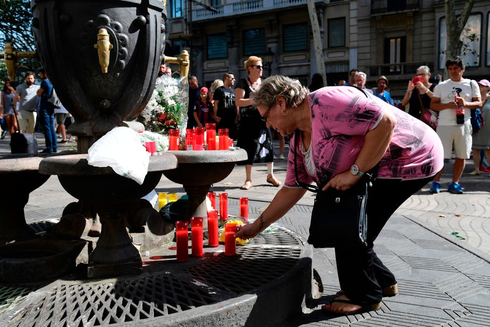 A woman lights a candle at the Canaletas fountain.