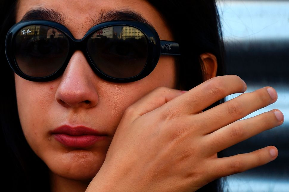 A woman cries as she observes a minute of silence in Puerta del Sol, Madrid, for the victims of Thursday's twin attacks in Sp