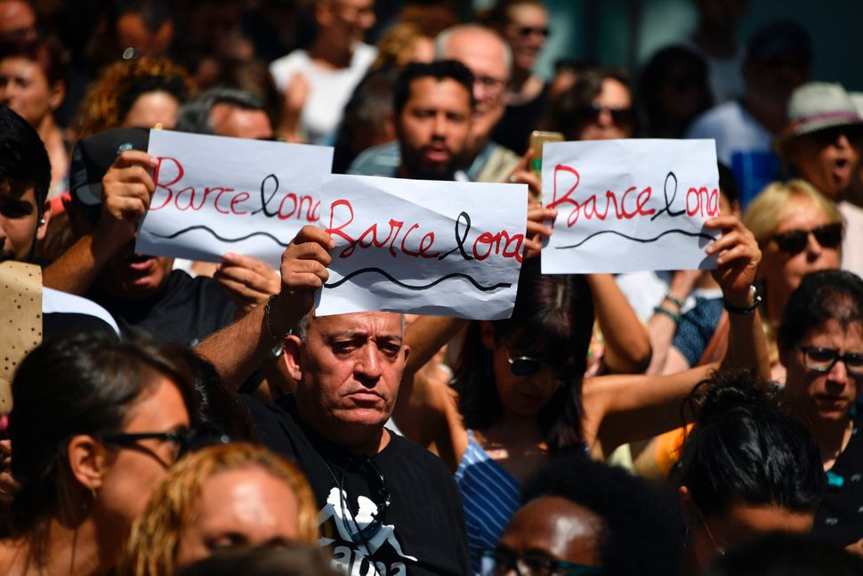 People hold aloft written signs displaying Barcelona's name before observing a minute of silence.