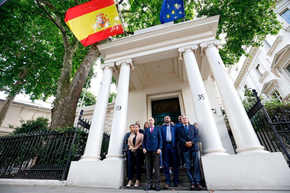 Staff at the Spanish Embassy in London pause for a minute's silence.