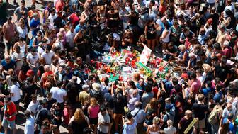 People gather to leave candles, flowers, messages, stuffed toys and many differents objects for the victims on August 18, 2017 at the spot where yesterday a van ploughed into the crowd, killing 13 persons and injuring over 100 on the Rambla boulevard in Barcelona. Drivers have ploughed on August 17, 2017 into pedestrians in two quick-succession, separate attacks in Barcelona and another popular Spanish seaside city, leaving 13 people dead and injuring more than 100 others. In the first incident, which was claimed by the Islamic State group, a white van sped into a street packed full of tourists in central Barcelona on Thursday afternoon, knocking people out of the way and killing 13 in a scene of chaos and horror. Some eight hours later in Cambrils, a city 120 kilometres south of Barcelona, an Audi A3 car rammed into pedestrians, injuring six civilians -- one of them critical -- and a police officer, authorities said. / AFP PHOTO / Josep LAGO        (Photo credit should read JOSEP LAGO/AFP/Getty Images)
