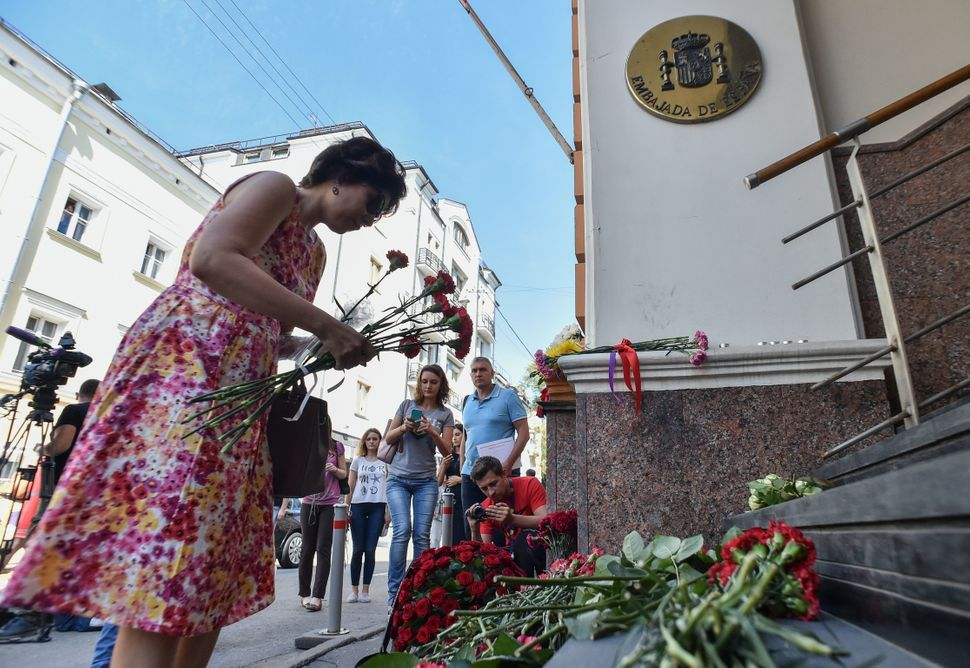 People place flowers to pay tribute to the victims of the Barcelona attack, in front of the Spanish embassy in Moscow.