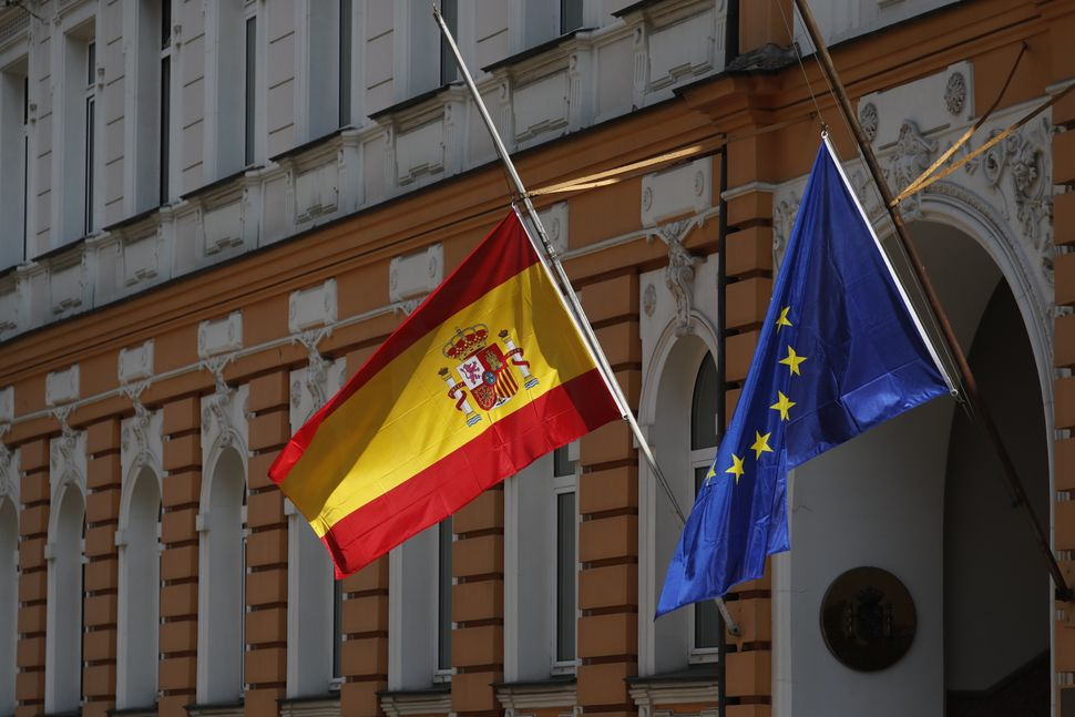 Flags of Spain and the European Union flying at half-mast outside the Embassy of Spain in Russia's capital.
