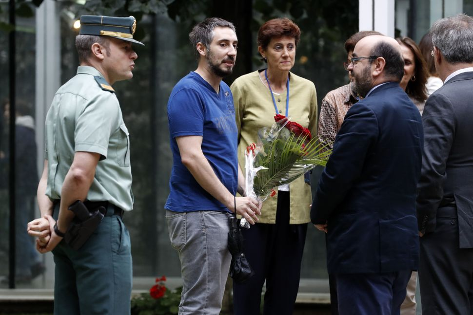 A man brings a bunch of flowers at the Embassy of Spain in Paris.