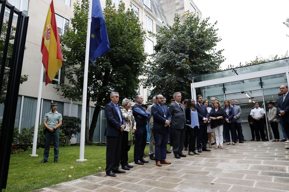 Staff members of the Embassy of Spain in Paris observe a minute of silence.