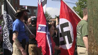 Demonstrators carry confederate and Nazi flags during the Unite the Right free speech rally at Emancipation Park in Charlottesville, Virginia, USA on August 12, 2017.  (Photo by Emily Molli/NurPhoto via Getty Images)