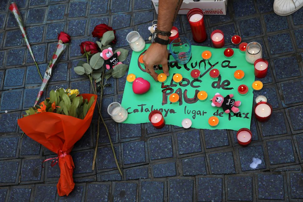 """A person places a candle on a placard, reading in Spanish and Catalan """"Catalonia, place of peace""""."""