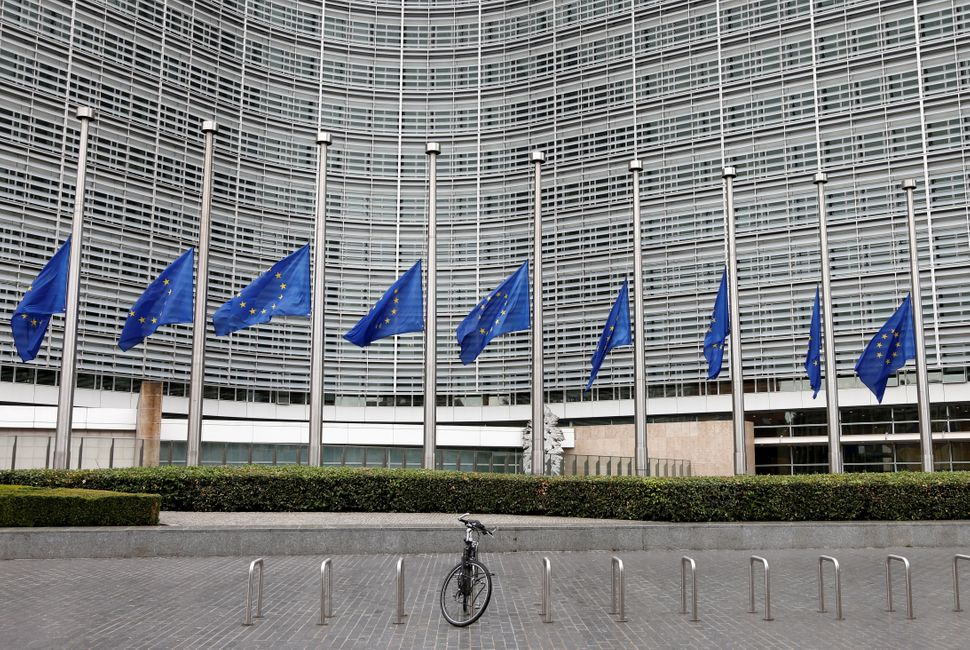 European Union flags are lowered at half-staff outside the European Commission headquarters in Brussels, Belgium.