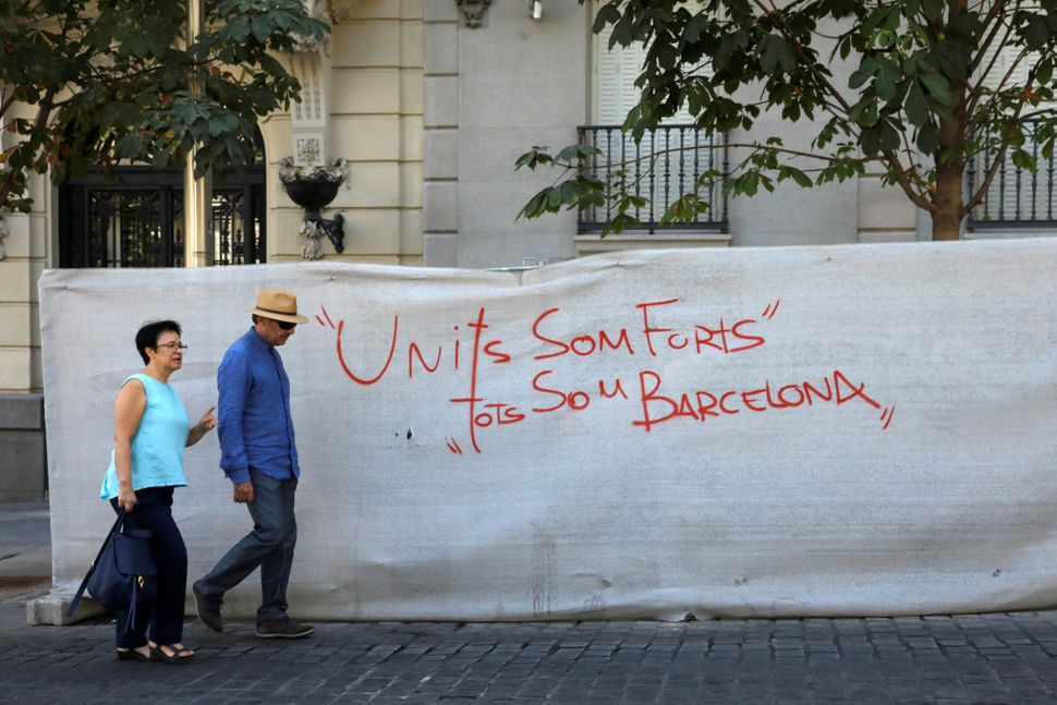 """A couple walks past a graffiti message that reads, """"United we are strong, we are all Barcelona"""" in the Spanish capital of Mad"""