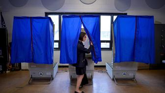 "A voter leaves the booth after casting her ballot in the Pennsylvania primary at a polling place in Philadelphia, Pennsylvania, U.S., April 26, 2016. Nearly half of Americans believe that the system that U.S. political parties use to pick their candidates for the White House is ""rigged"" and two-thirds want to see the process changed, according to a Reuters/Ipsos poll.  REUTERS/Charles Mostoller/File Photo"