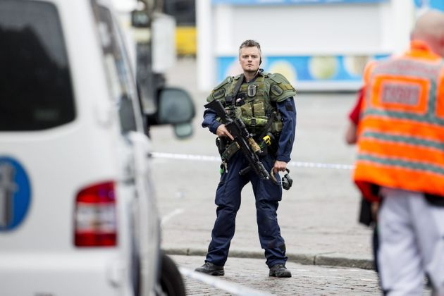An armed police officer stands guard at the Turku Market Square in the Finnish city of Turku where several...