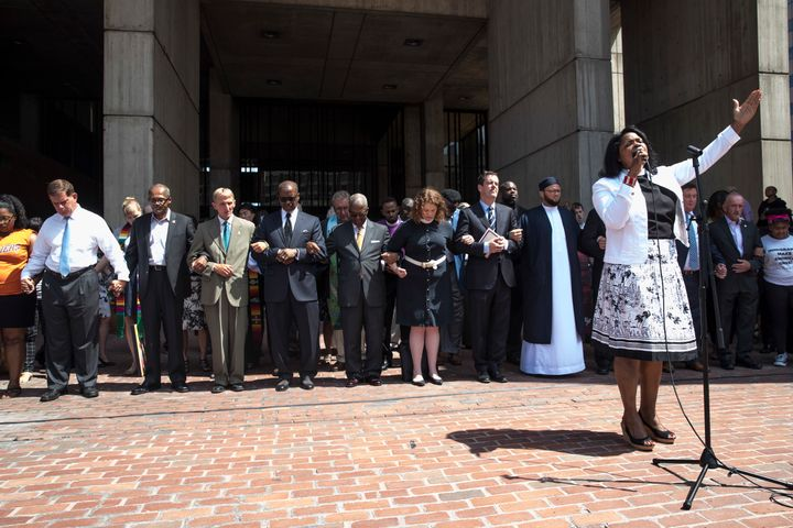 The Rev. Arlene Hall leads a prayer for peace at City Hall Plaza, as Boston Mayor Marty Walsh and Police Commissioner William B. Evans hold hands with clergy ahead of Saturday's rally.