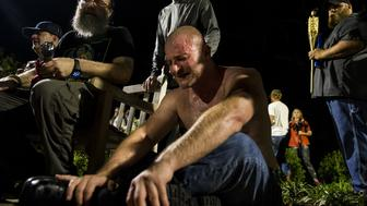 CHARLOTTESVILLE, USA - AUGUST 11:A man cringes after being hit in the face with pepper spray during a clash between counter protestors and Neo Nazis, Alt-Right, and White Supremacist groups after they marched through the University of Virginia Campus with torches in Charlottesville, Va., USA on August 11, 2017. (Photo by Samuel Corum/Anadolu Agency/Getty Images)