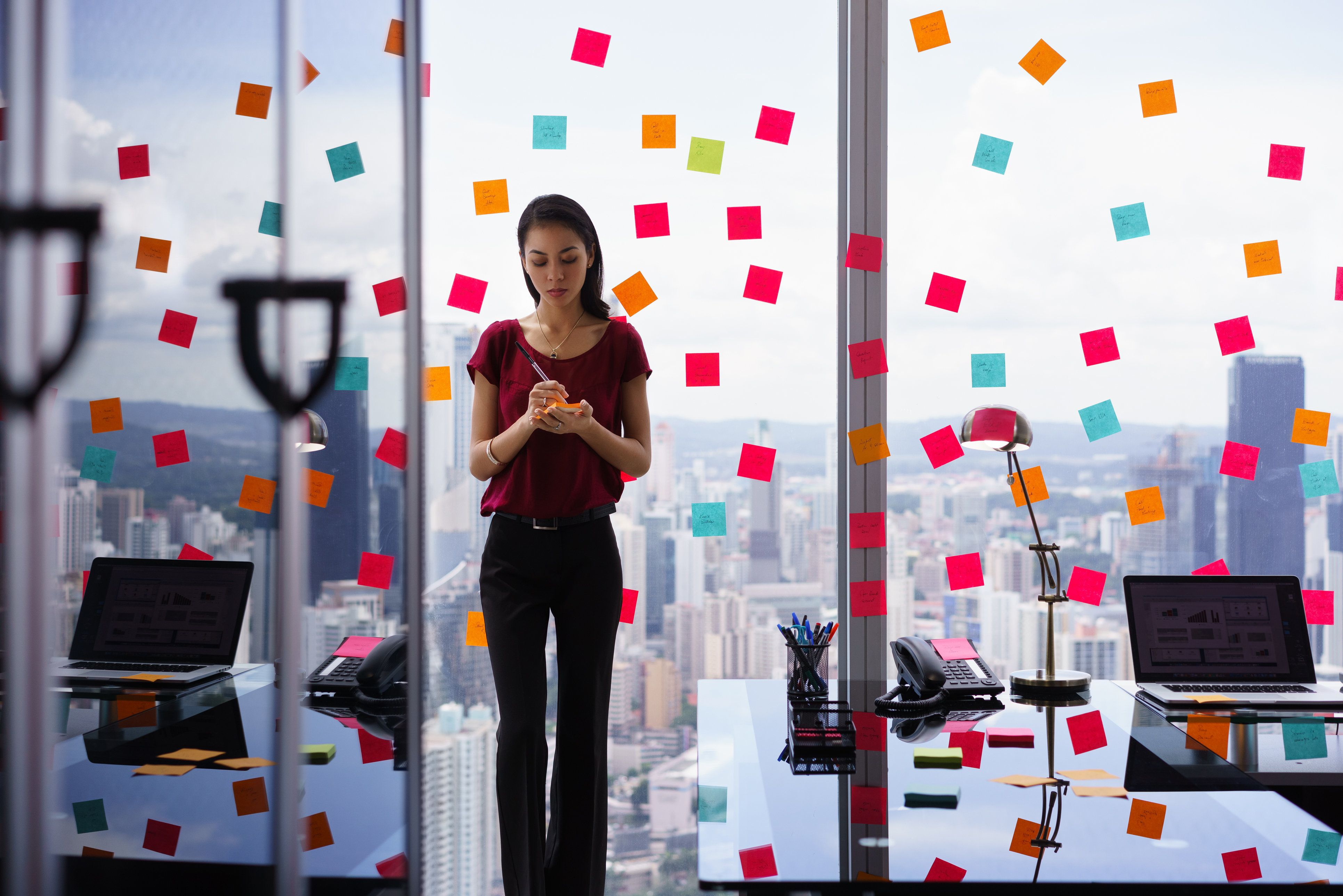 Mixed race secretary working in modern office in skyscraper, writing and sticking adhesive notes with tasks on window.
