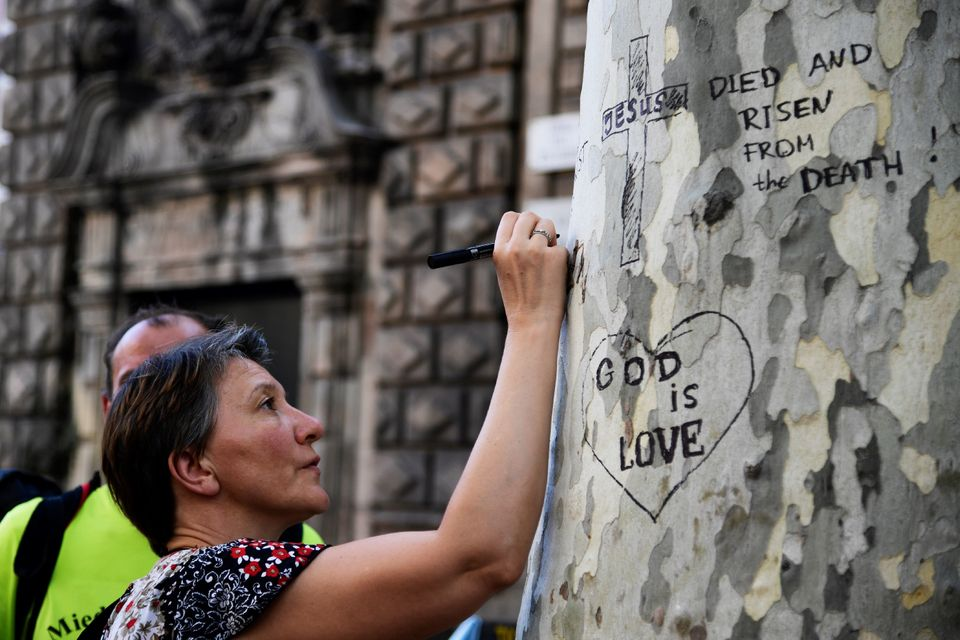 A woman writes a message on a tree at Plaza de Catalunya on