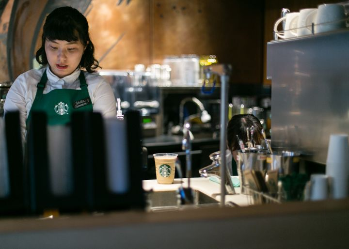 A Starbucks employee prepares drinks for customers inside Kyoto's new Starbucks branch on June 30, 2017.