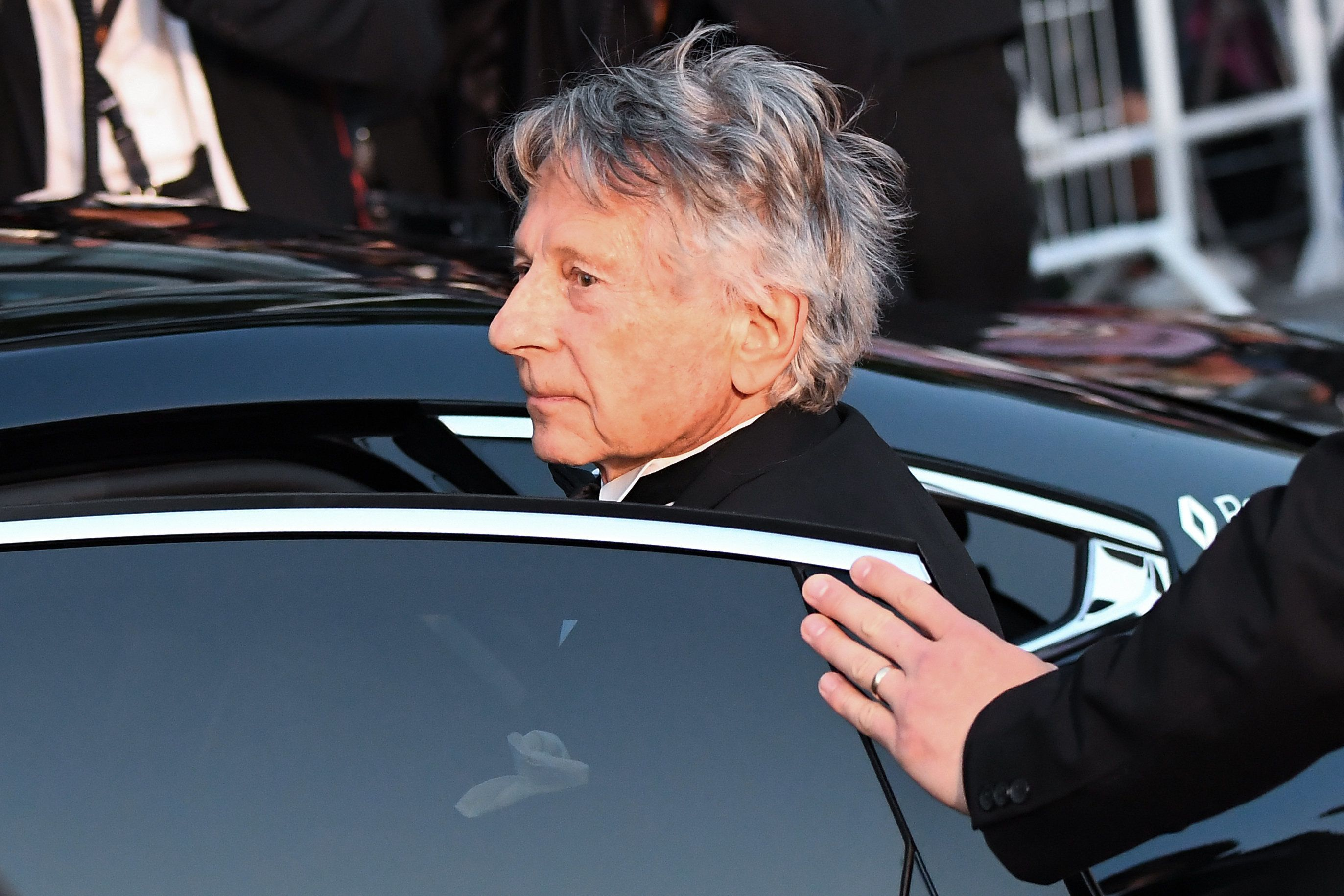 (FromL) French-Polish director Roman Polanski gets into a car as he leaves the Festival Palace on May 27, 2017 following the screening of the film 'Based on a True Story' (D'Apres une Histoire Vraie) at the 70th edition of the Cannes Film Festival in Cannes, southern France.  / AFP PHOTO / Anne-Christine POUJOULAT        (Photo credit should read ANNE-CHRISTINE POUJOULAT/AFP/Getty Images)