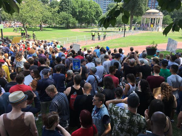 Counterprotesters stand at the edge of their barricade as the 'Boston Free Speech' rally takes place inside the bandstand in