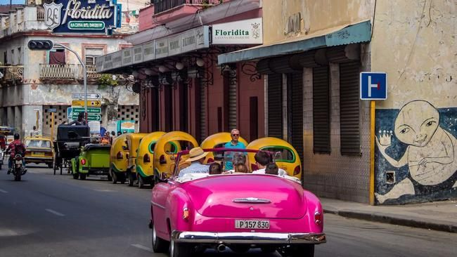 A vintage car drives to the Floridita bar in Old Havana, Hemingway's favorite.
