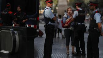 Pilar Revilla, 75, gets emotional after hugging a Catalan Mossos d'Esquadra officer after visiting an impromptu memorial where a van crashed into pedestrians at Las Ramblas in Barcelona, Spain, August 20, 2017. REUTERS/Susana Vera