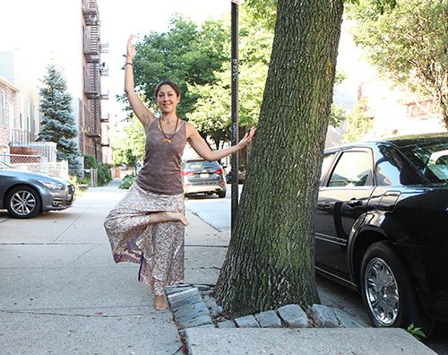 <strong>Sylvia doing a tree pose at a tree.</strong>