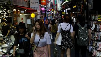 SEOUL, SOUTH KOREA - AUGUST 11:  Pedestrians walk past at the Myeongdong shopping district on August 11, 2017 in Seoul, South Korea. North Korea have announced they are preparing to launch missiles toward U.S. Pacific territory of Guam.  (Photo by Chung Sung-Jun/Getty Images)