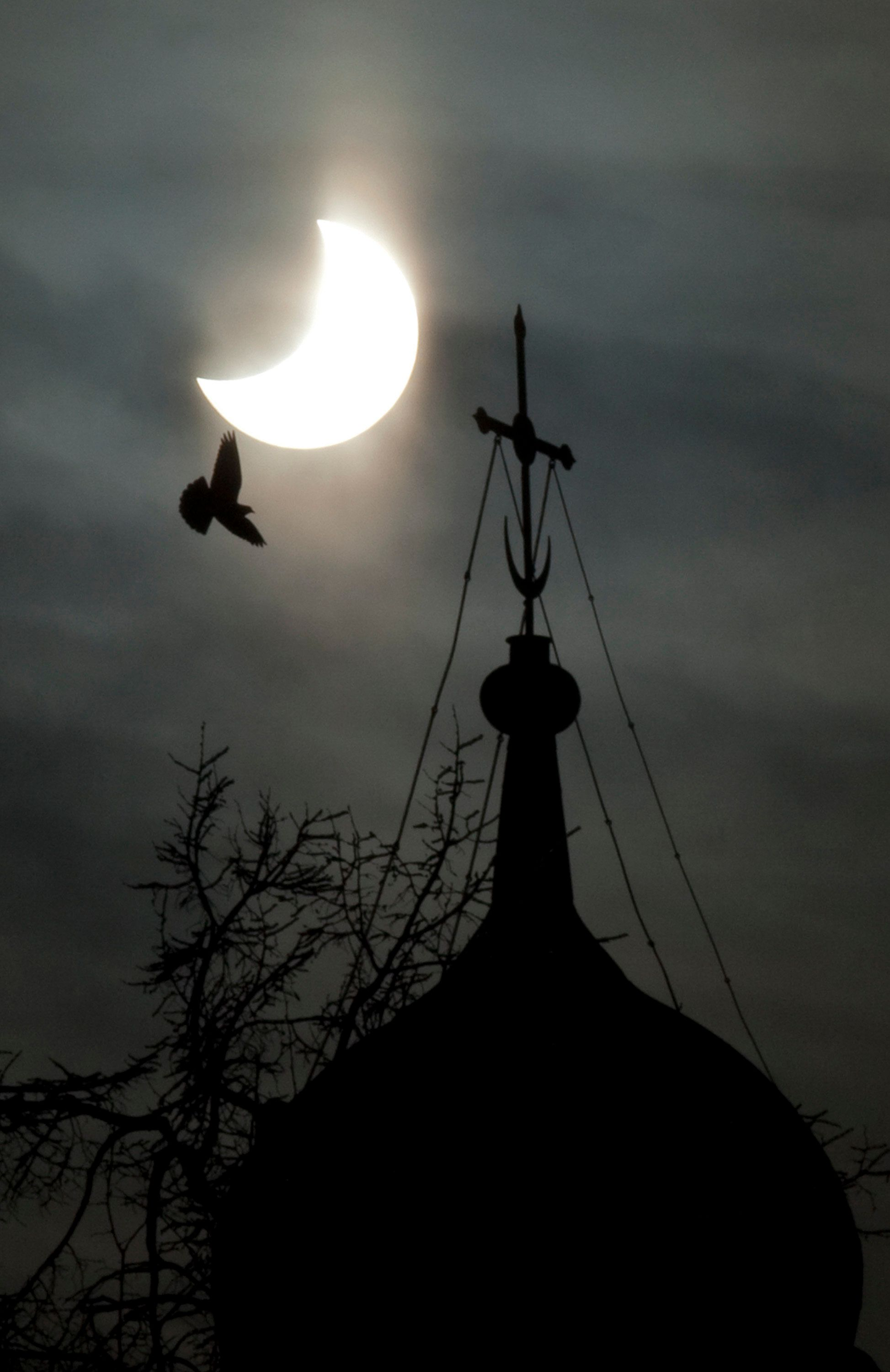 A partial solar eclipse of the sun is seen above a dome of the Life-giving Trinity Russian Orthodox Cathedral in Moscow on January 4, 2011. Europe was given a front-row seat today to the first solar eclipse of 2011 only to find that in many places a thick curtain of cloud marred the spectacle. AFP  PHOTO / OXANA ONIPKO (Photo credit should read OXANA ONIPKO/AFP/Getty Images)
