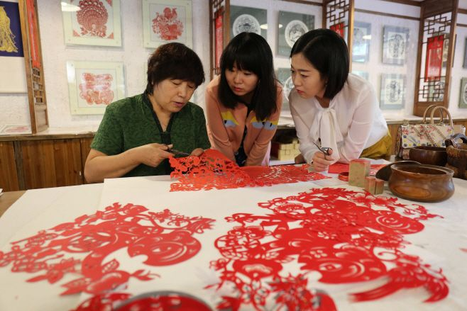 Tourists are learning one of the traditional paper cutting techniques in Chengde, Hebei province, China./ Source: Xinhua
