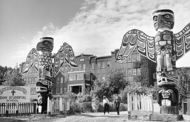 Students walk between two totem poles at St. Michael's Indian Residential School in Alert Bay, British Columbia, in a 1970 ph